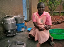 A young schoolgirl demonstrates how she prepares meals outdoors over an improved cookstove - a drastic improvement in terms of health and fuel consumption compared to the traditional 3-stone fire.